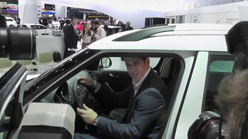 Евгений позирует за рулем автомобиля