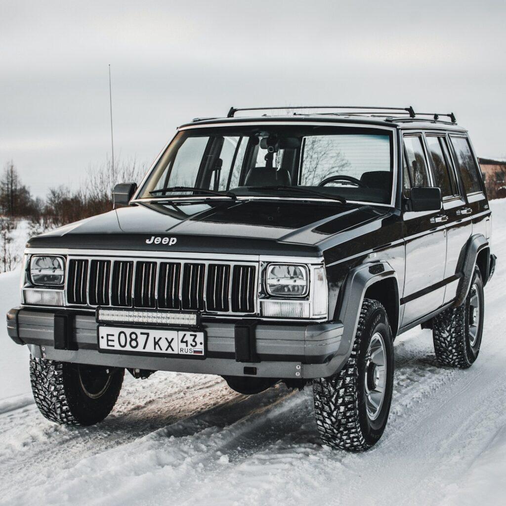 Черный Jeep Cherokee в белоснежном лесу: лучший контраст